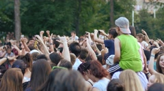 Cheering crowd people fan spectators audience by concert stage jump raise hands - stock footage