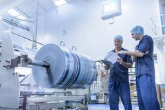 Workers in discussion in food packaging printing factory Stock Photos