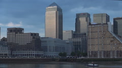 Boat sailing on Thames river and airplane crossing sky Canary Wharf view. - stock footage