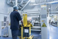 Worker unloading printed roll in food packaging printing factory Stock Photos