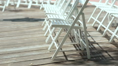 White chairs on a wooden platform in the open air Stock Footage