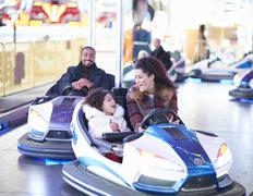 Mother and daughter in bumper car face to face smiling - stock photo