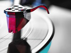 Close up of red turntable stylus playing a vinyl record Stock Photos