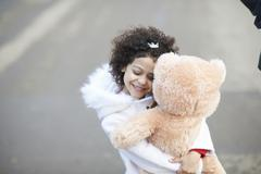 High angle view of girl, eyes closed hugging soft toy Stock Photos