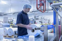 Worker moving roll of packaging in food packaging printing factory - stock photo