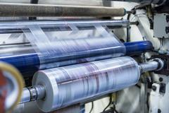 Rolls of printed plastic film in food packaging printing factory - stock photo