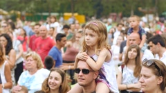 People crowd spectators of concert kid girl sit on father shoulders to see stage - stock footage