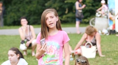 Cute little teen age girl enjoy listen to music from phone player and singing Stock Footage