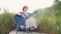 Young redhead girl playing guitar in park near the reed Stock Footage