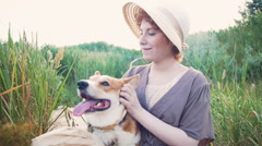 Happy corgi dog with the owner girl in the park near the reed Stock Footage