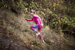 Side view of young woman wearing sport wear running up hill - stock photo