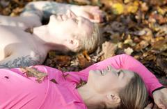 Side view of couples head and shoulders lying on autumn leaves looking up - stock photo