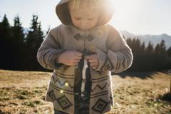 Female toddler fastening hooded jacket, Tegernsee, Bavaria, Germany Stock Photos