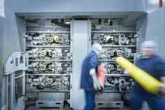 Workers loading printing plates into printer in food packaging printing factory Stock Photos