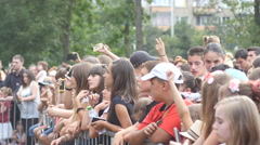 Teen age kids spectators fans by stage enjoy music concert cheerfully raise hand Stock Footage