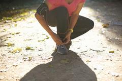Waist down of mature woman crouching down tying shoelace - stock photo