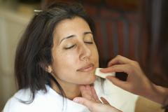 Hands of female make up artist applying foundation to clients face - stock photo