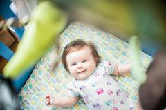 Overhead view of baby girl lying in crib smiling Stock Photos