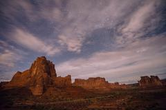 Clouded starry sky and valley rock formations at night, Moab, Utah, USA - stock photo