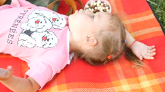 Little kid girl lying on a rug - family picnic in park - play walk with child Stock Footage
