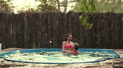 Tanned guy and a slender girl play in the pool. Slow motion - stock footage