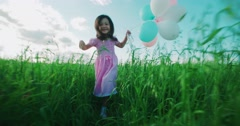 Little Asian girl in a dress running through green wheat field with balloons in Stock Footage