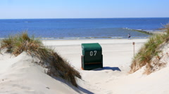 Dunes with a traditional green Baltic beach chair Strandkorb Stock Footage
