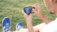 Man in picnic slide type his smart phone in social media instead of be active Stock Footage