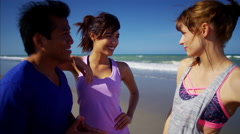 Smiling multi ethnic friends enjoying fitness activity on the beach Stock Footage