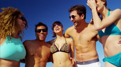 Young multi ethnic people wearing swimsuits and sunglasses relaxing on the beach Stock Footage