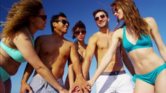 Multi ethnic group of friends in swimwear having fun on their beach holiday Stock Footage