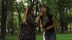 Two cute girls having fun smoke e-cigarette and soap bubbles in the park Stock Footage