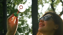 Cute girl with sunglasses playing with the soap bubble in the park Stock Footage