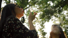 Beautiful girls having fun smoke e-cigarette and soap bubbles in the park - stock footage