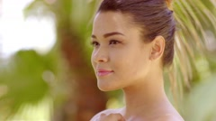 Close up on grinning woman near tropical tree Stock Footage