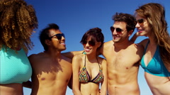 Happy multi ethnic people wearing swimsuits and sunglasses relaxing on the beach Stock Footage