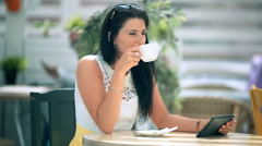 Happy young woman drinking coffee / tea and using tablet in a coffee shop Stock Footage