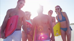 Multi ethnic males and females in swimwear relaxing with body board on the beach Stock Footage