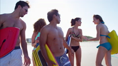 Multi ethnic people in swimwear enjoying body boarding on the beach Stock Footage