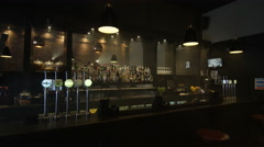 4K View of empty bar in city stacked with bottles & draught beer pumps No people Stock Footage