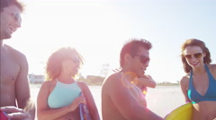 Multi ethnic group of students in swimwear with bodyboards on the beach Stock Footage