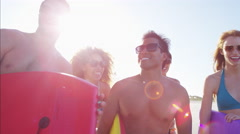 Portrait of multi ethnic males and females relaxing with bodyboard on the beach Stock Footage
