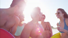 Multi ethnic males and females in swimsuits with body boards on beach vacation Stock Footage