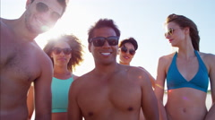 Multi ethnic people in swimsuits enjoying body boarding on the beach Stock Footage