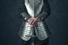 Weathered hands of knight holding sword. - stock photo