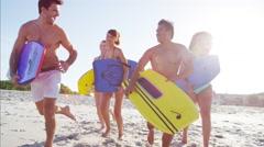 Multi ethnic friends in swimwear running with bodyboards on the beach Stock Footage