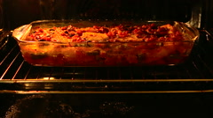 Dish of meat and potatoes is baked in a glass bowl in the oven stoves - stock footage
