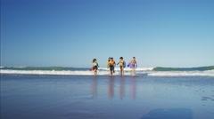 Multi ethnic friends in swimwear jogging with bodyboards on the beach Stock Footage