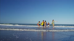 Multi ethnic males and females in swimwear jogging with bodyboards on the beach Stock Footage