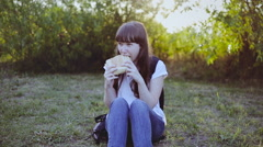 Young woman spending a day in nature and eating a sandwich at sunset - stock footage
